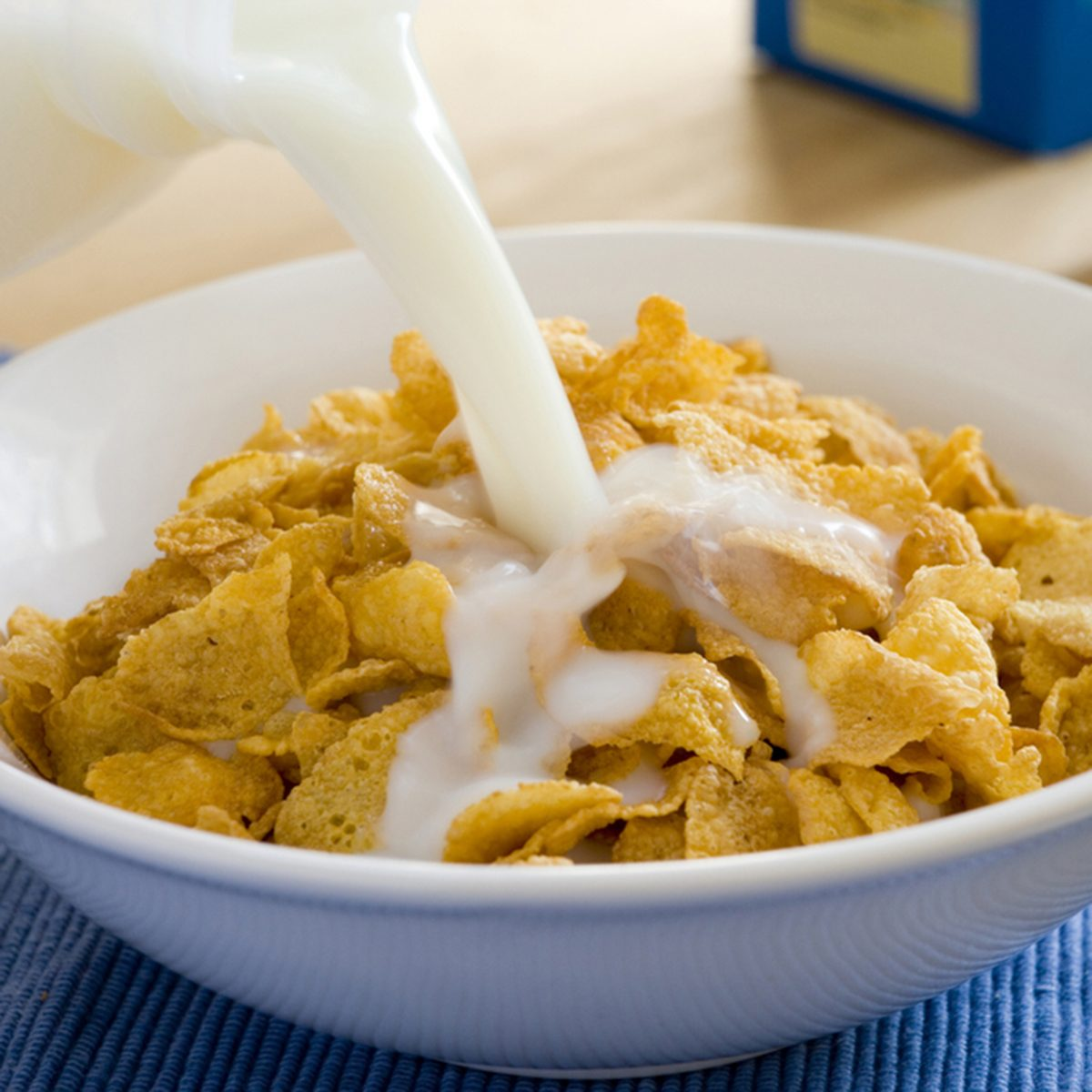 milk being poured into a bowl of cereal