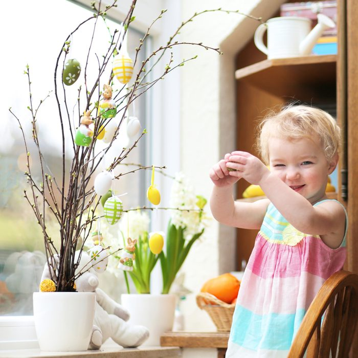 Adorable little blonde toddler girl decorating with Easter eggs cherry tree branches standing in the kitchen next a window with garden view; Shutterstock ID 179985827