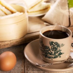Steaming traditional oriental Chinese kopitiam style dark coffee in vintage mug and saucer with coffee beans. Fractal on the cup is generic print. Soft focus with dramatic light on wooden background