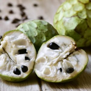 closeup of some custard apples, one of them cut in half, on a rustic wooden surface