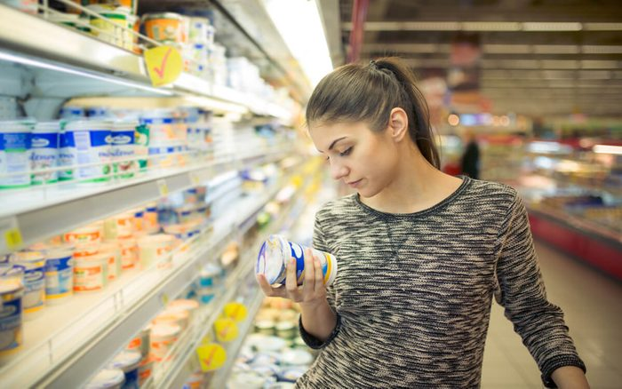 Young woman reading ingredients,declaration or expiration date on a dairy product before buying it.Curious woman reading nutritional values of the food.Shopping in the supermarket grocery store