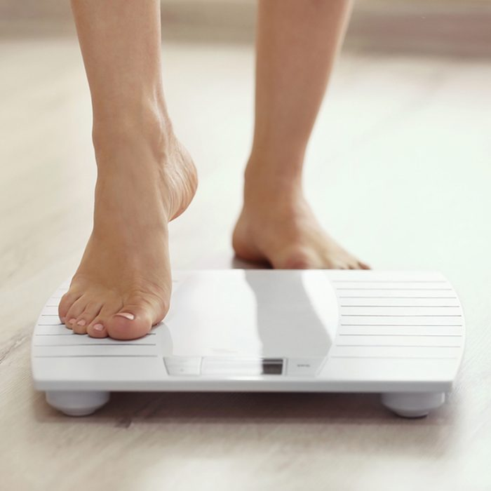 Female leg stepping on floor scales; Shutterstock ID 461066953