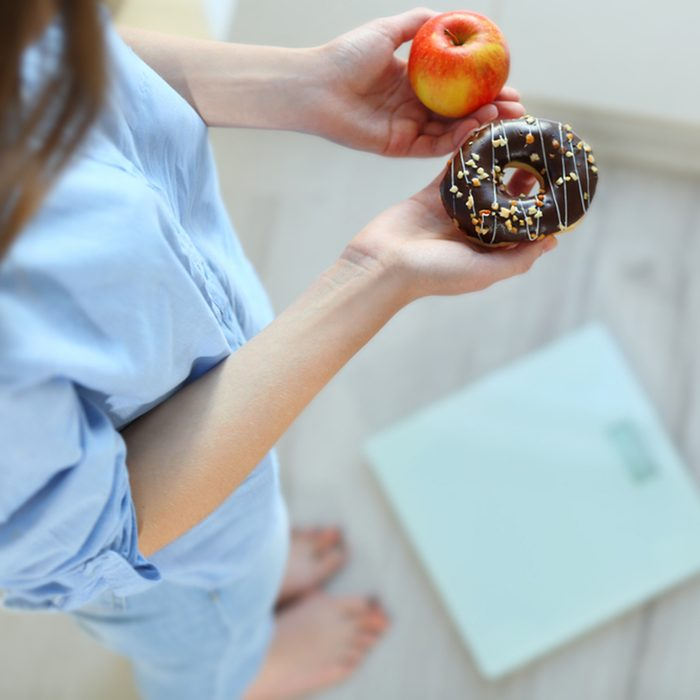 Close up view of woman making choice between apple and donut with blurred scales on background. Dieting concept; Shutterstock ID 517231915; Job (TFH, TOH, RD, BNB, CWM, CM): TOH