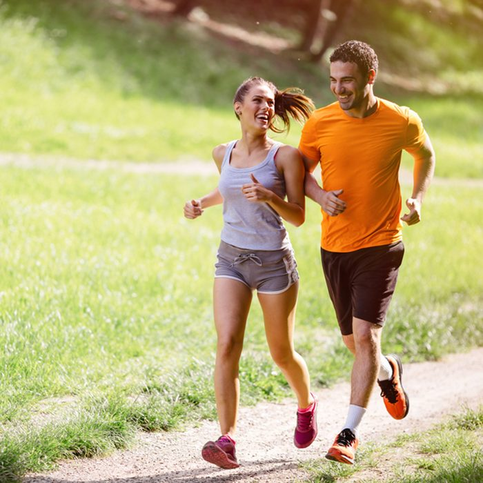 Couple jogging and running outdoors in nature; Shutterstock ID 527013196