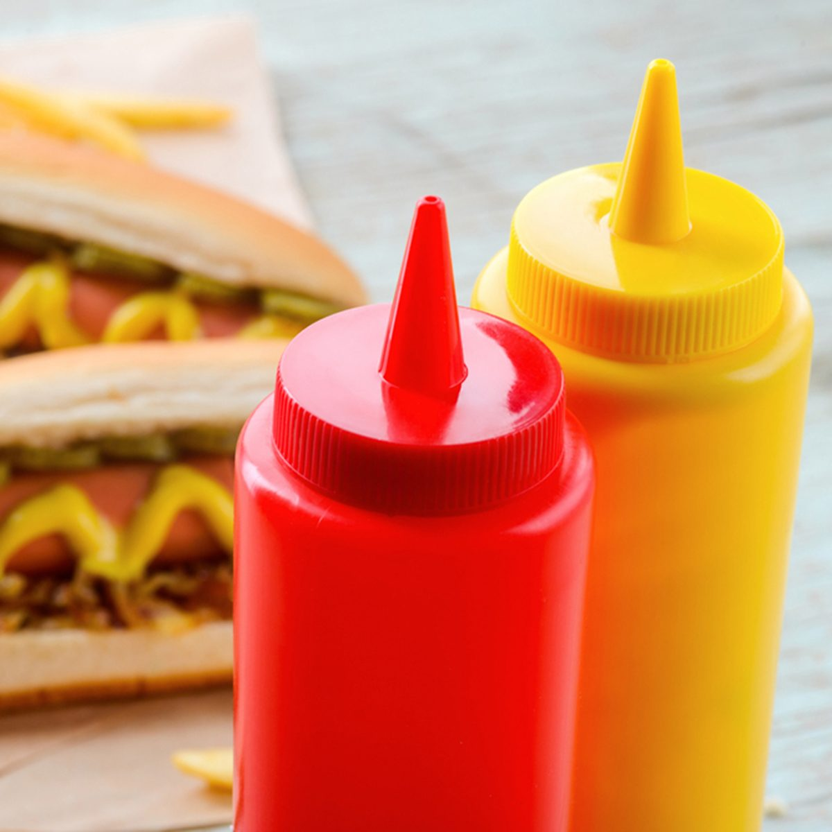 Ketchup and mustard bottles, close-up. Traditional hot dogs and potatoes on the background, baking paper. Western diet