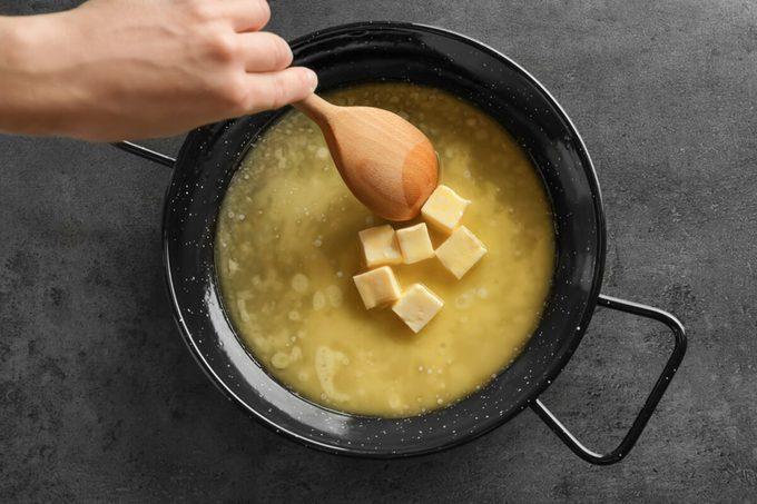 Woman stirring melting butter on frying pan, closeup