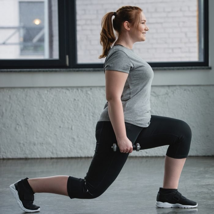 Obese girl performing lunges with dumbbell in gym; Shutterstock ID 1030981678