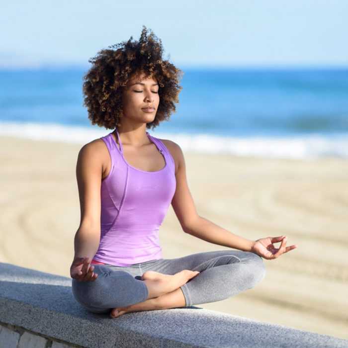 Black woman, afro hairstyle, doing yoga asana in the beach with eyes closed. Young Female wearing sport clothes in lotus pose with defocused background.; Shutterstock ID 788029807