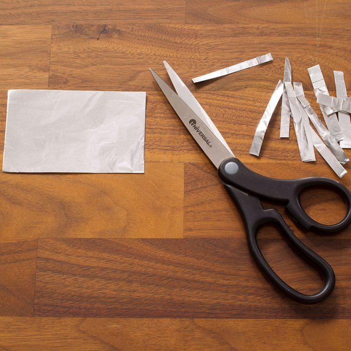 Using scissors to cut foil