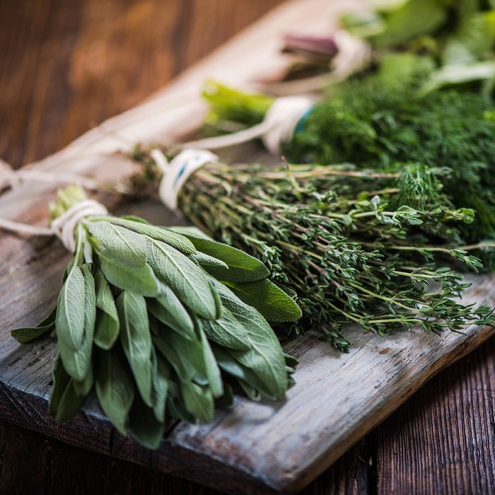 Basil,sage,dill,and thyme herbs on wooden board preparing for winter drying