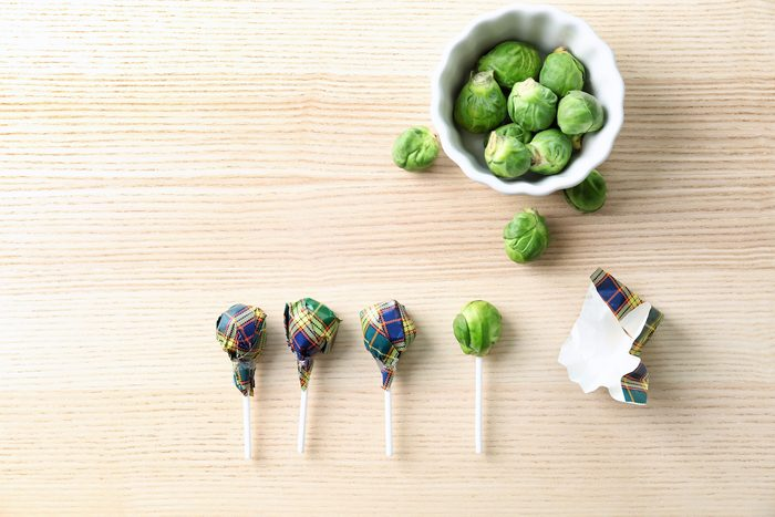 Brussel sprouts with lollipop sticks in candy wrappers on table. April fools food pranks.