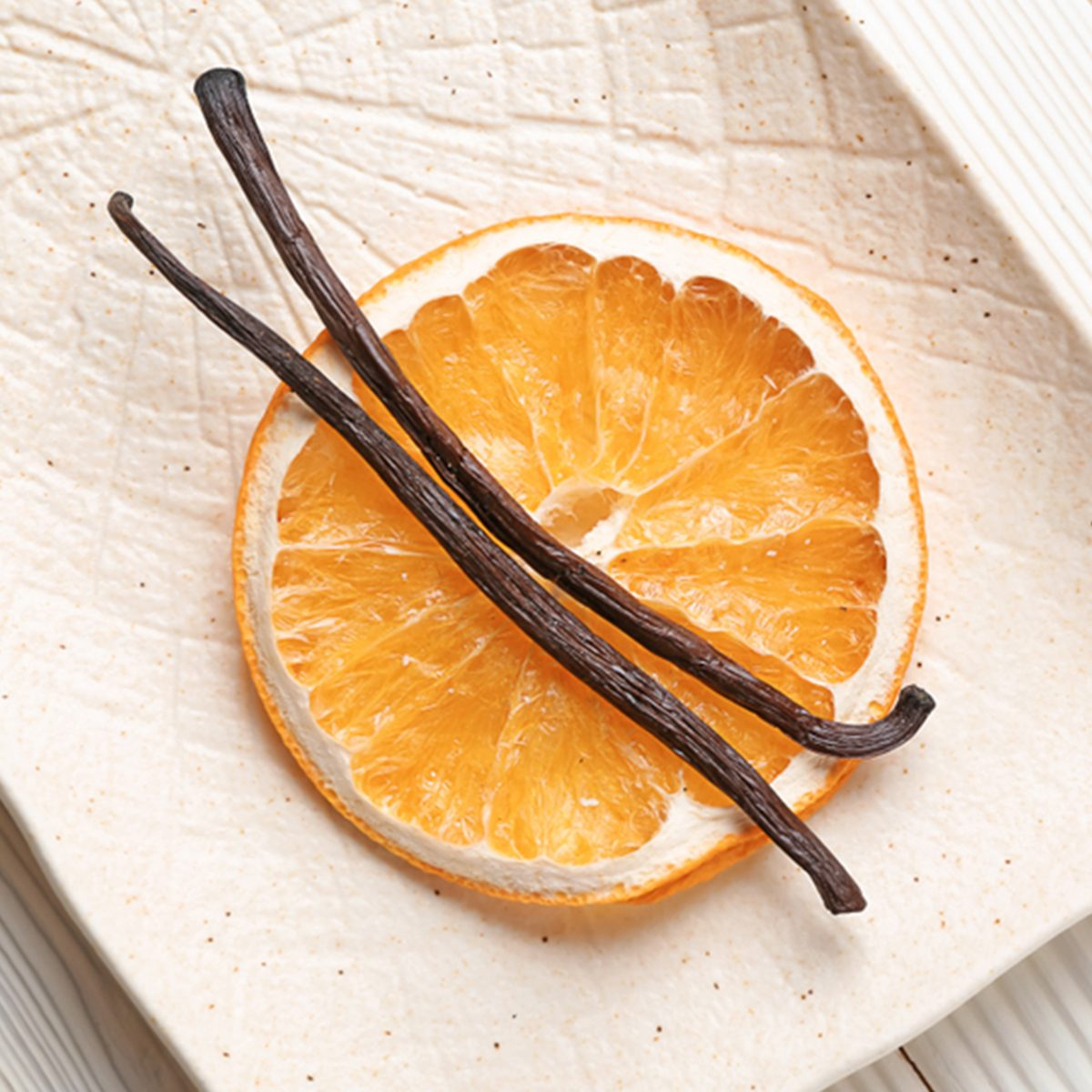 Plate with dry orange slice and aromatic vanilla sticks on white wooden background; Shutterstock ID 1283600635; Job (TFH, TOH, RD, BNB, CWM, CM): TOH