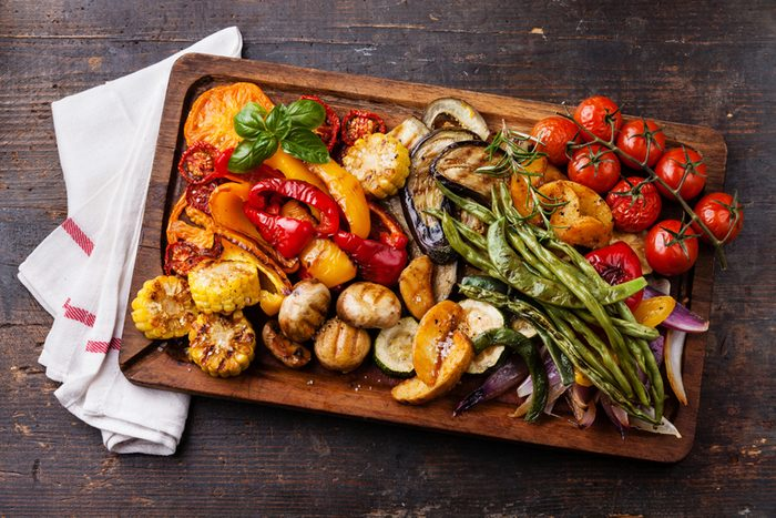 Grilled vegetables on cutting board on dark wooden background