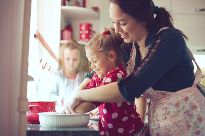 Mother with her 5 years old kids cooking holiday pie in the kitchen to Mothers day