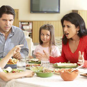Young Hispanic Family Enjoying Meal At Home