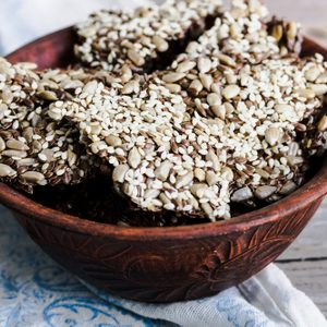 crackers from flax seed, sesame, sunflower and spices on a dark plate, healthy snack; Shutterstock ID 341237888