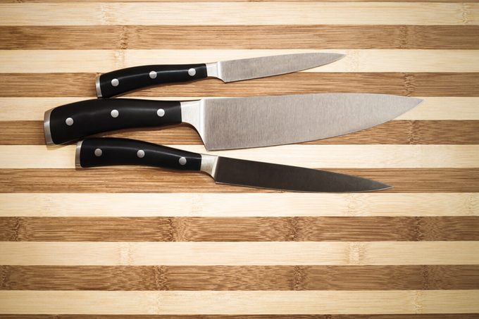 three kitchen knives over bamboo cutting board