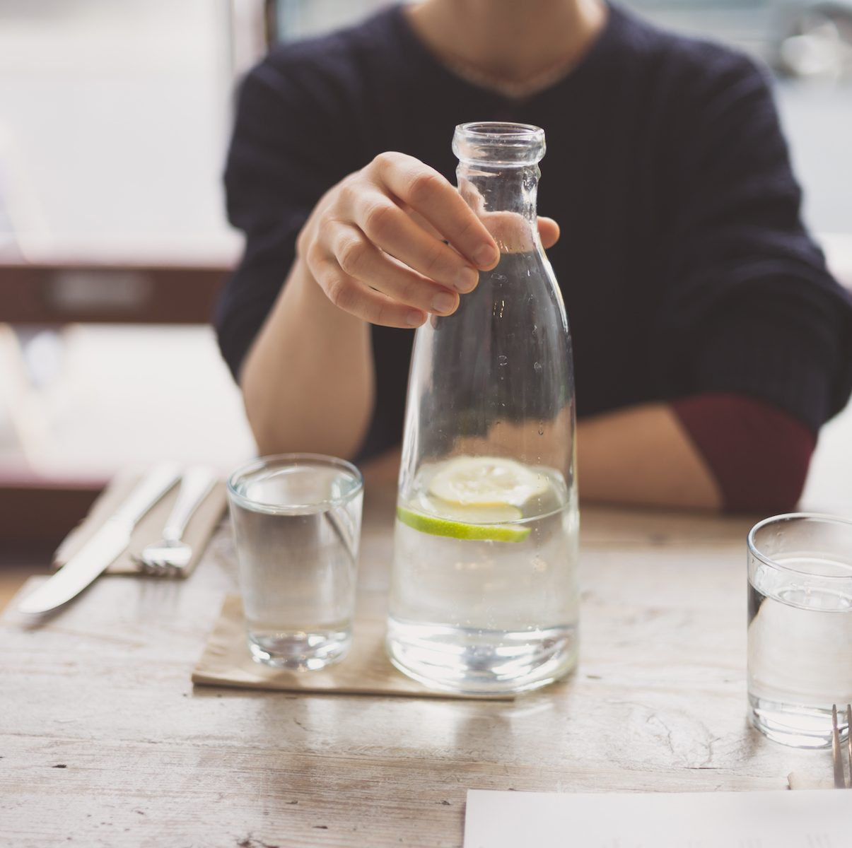 A young woman is sitting at a table in a restaurant and is drinking water