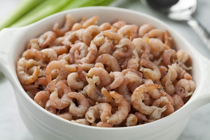 Bowl with peeled brown shrimps close up