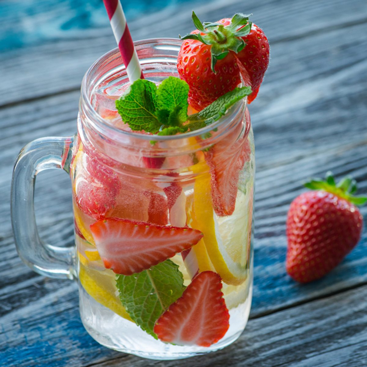 Jug with lemon and strawberry infused water on a rustic wooden table