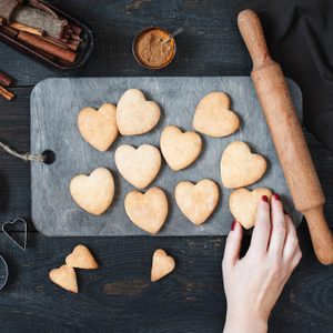 Female hand holding the baked cookies-hearts on the vintage wooden table