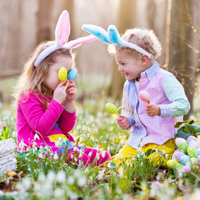 Kids on Easter egg hunt in blooming spring garden. Children with bunny ears searching for colorful eggs in snow drop flower meadow. Toddler boy and preschooler girl in rabbit costume play outdoors.; Shutterstock ID 582357538
