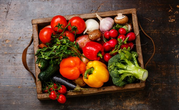 Fresh vegetables in wooden box on wooden background;