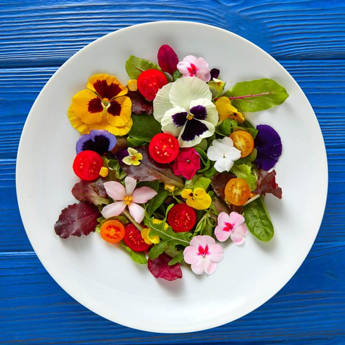 Edible flowers salad in a plate on blue wooden table with fork