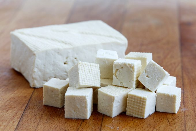 Single block of white tofu with cut tofu cubes on wooden chopping board