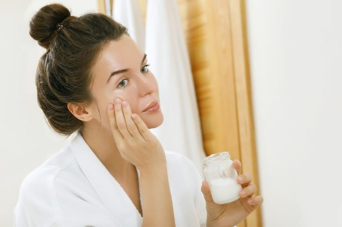Woman is moisturizing her skin with a coconut oil.