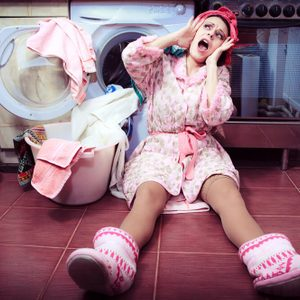 young housewife with washing machine and towels