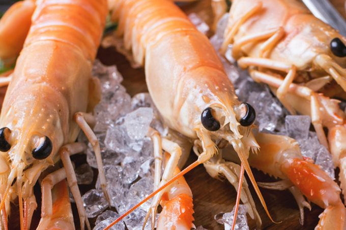 Raw langoustines on ice with herbs and lemon served on vintage cutting board over wooden table; Shutterstock ID 243778558; Job (TFH, TOH, RD, BNB, CWM, CM): Taste of Home
