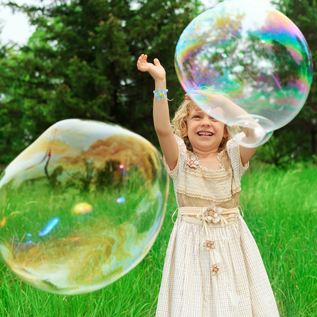 Pretty little girl is playing with big bubbles in a park