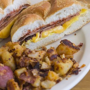 Taylor ham, pork roll, egg and cheese breakfast sandwich on a kaiser roll with salt pepper and ketchup and a side of home fries from New Jersey