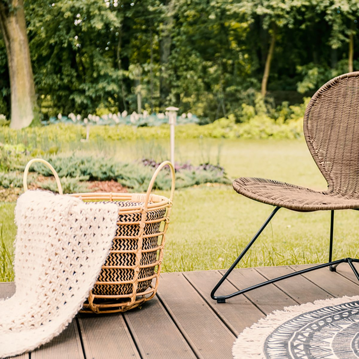 Close-up of a brown garden chair and a beige blanket in a basket on a wooden patio in the yard