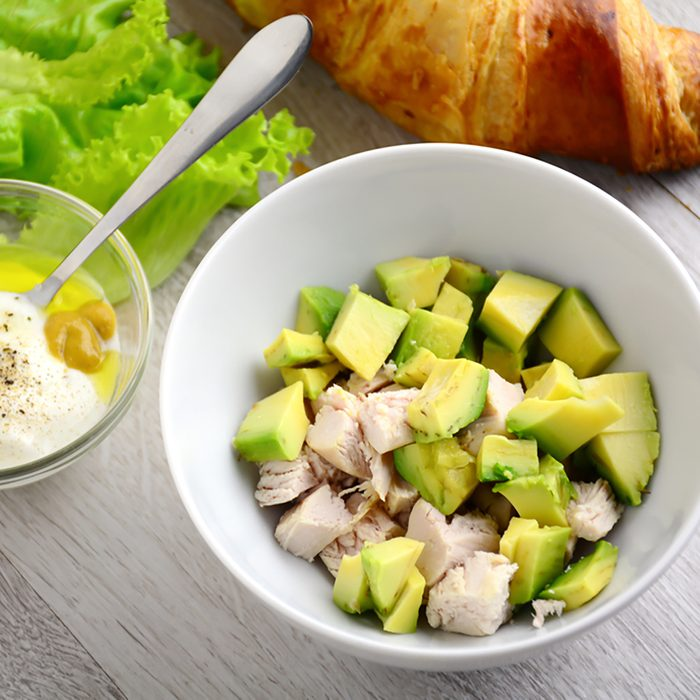 Preparing chicken avocado salad with light yogurt dressing on gray wooden table.