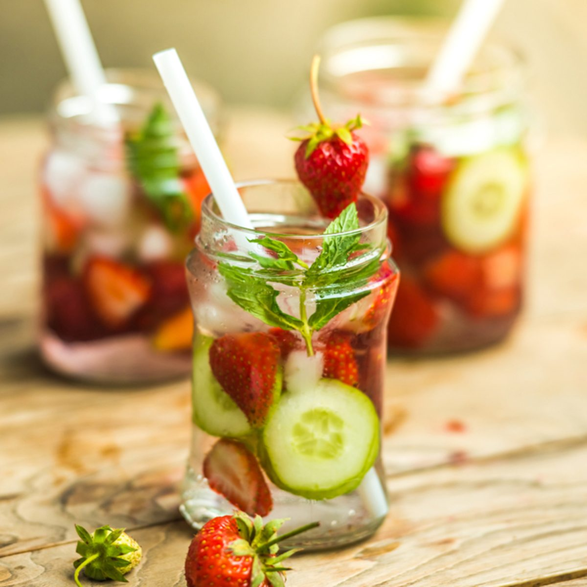 Three retro glass jars of lemonade with strawberries, cucumber and mint on wooden table