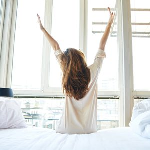 Woman stretching in bed after wake up, back view; Shutterstock ID 292934846