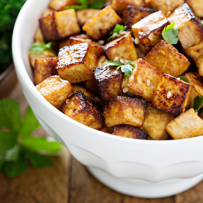 Stir fried tofu in a bowl with sesame and greens.