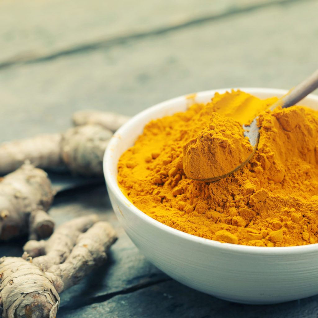 Turmeric powder and turmeric on wooden background - vintage effect style.; Shutterstock ID 407533114