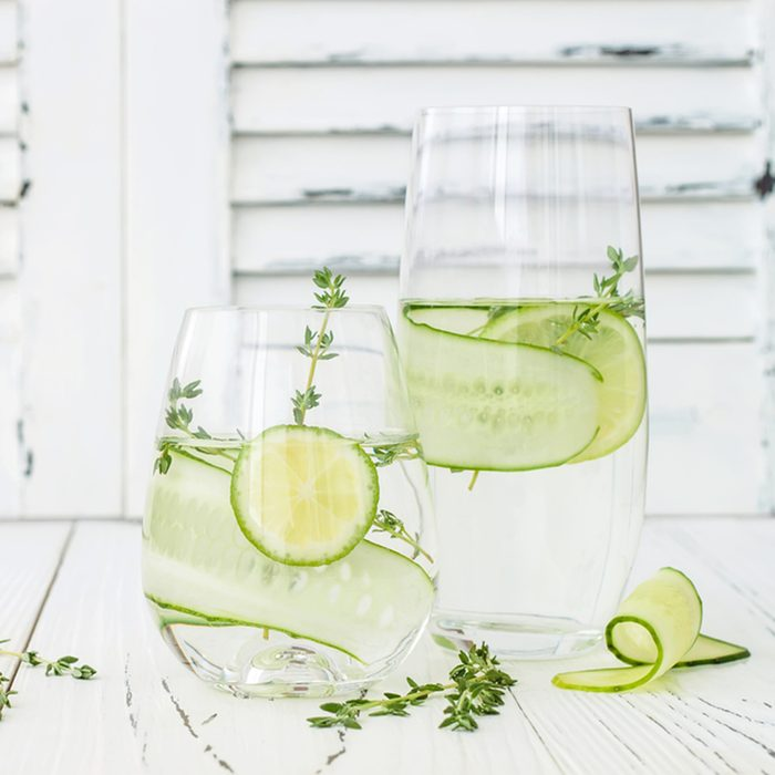 Cucumber infused hydrating water with thyme and lime. Homemade flavored lemonade on rustic old wooden table