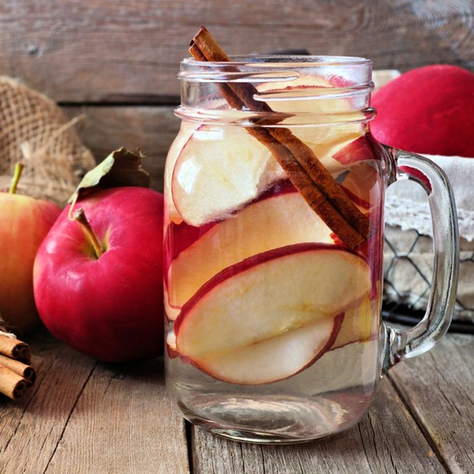 Autumn themed detox water with apple, cinnamon and red pear in a mason jar. Scene on rustic wood background