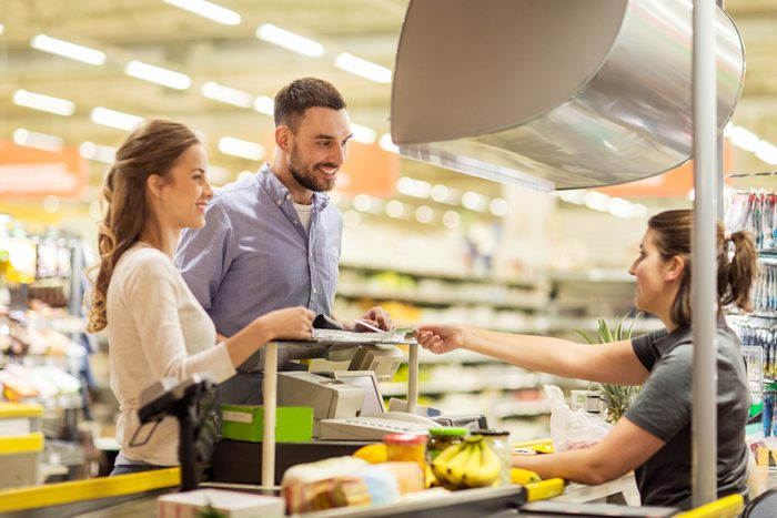 happy couple buying food at grocery store or supermarket cash register.
