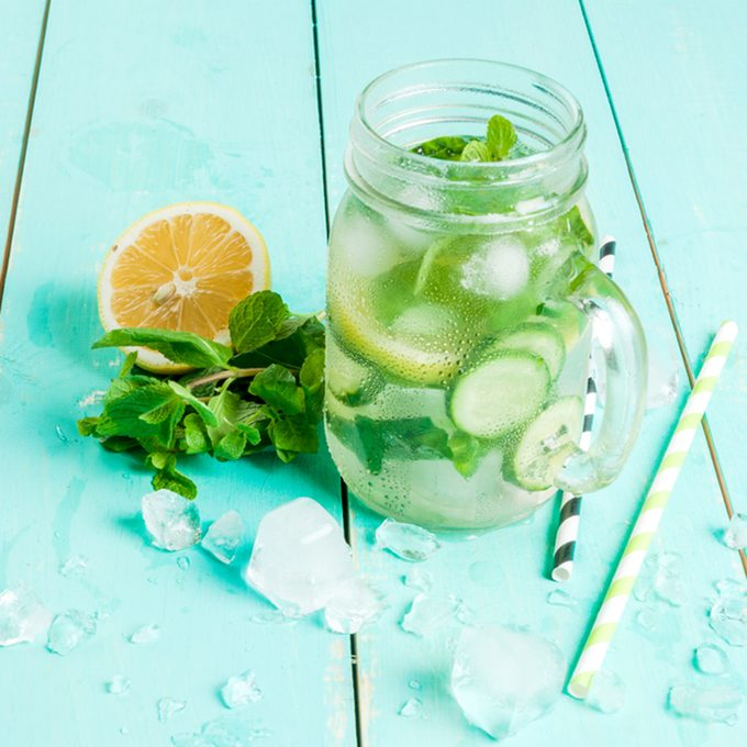 Refreshing summer drink - detox cocktail of mint, cucumber and lemon. On a light blue wooden table, bright sunlight, copy space
