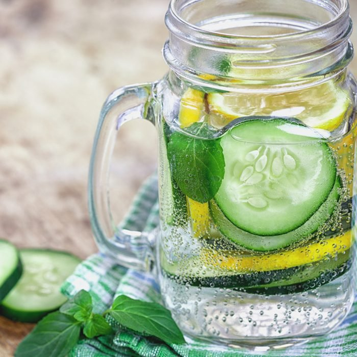 Detox Infused water with cucumber and lemon on wooden background