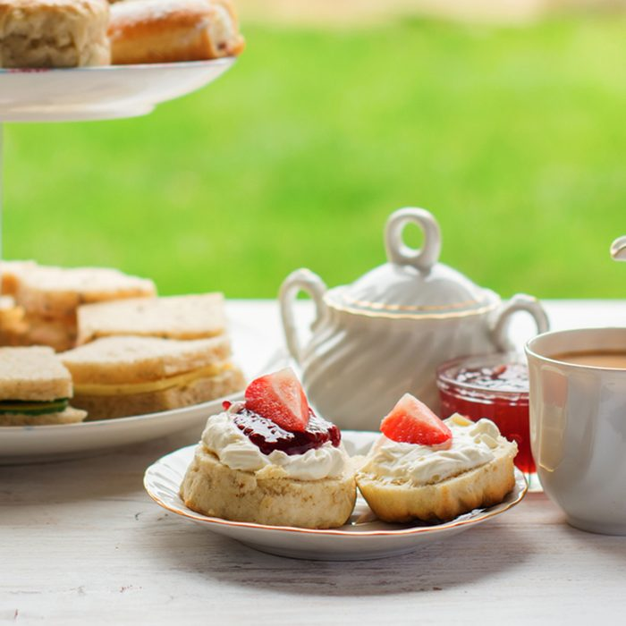 English afternoon teas in the garden cafe: scones with clotted cream and jam, strawberries, with various sandwiches on the background