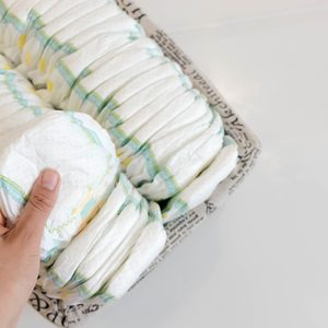 Stack of baby disposable diapers and Pacifier over white background.