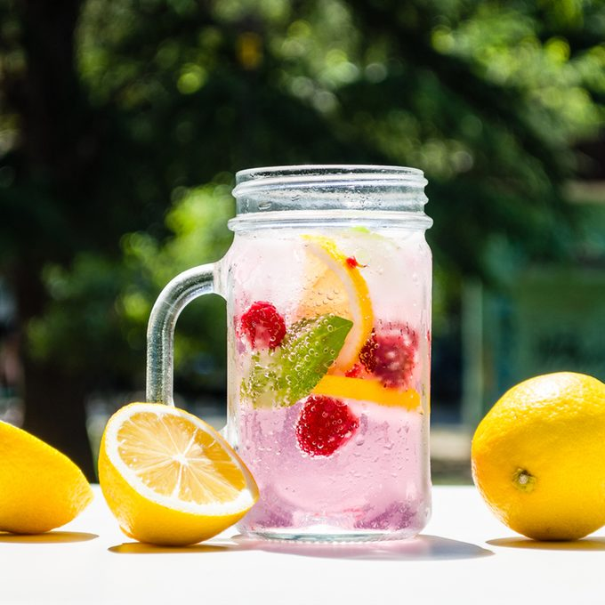 Healthy detox water served in a mason jar with ice lemon raspberries mint leaf bubbles and surrounded with green nature and trees into the background