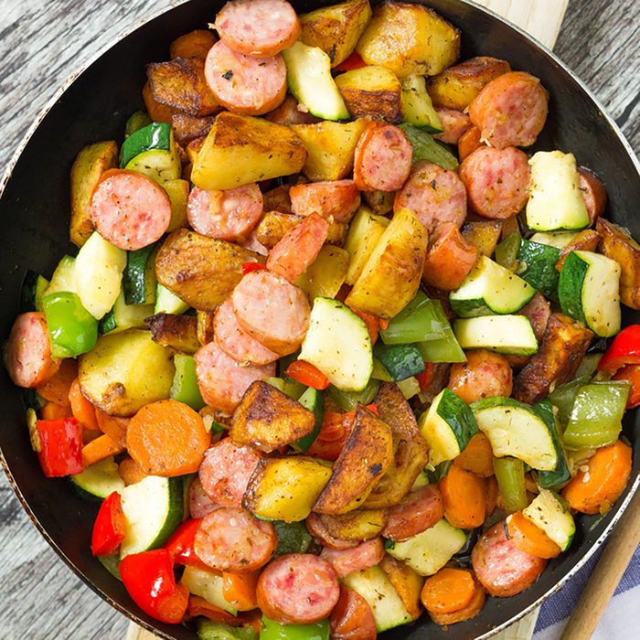 Freshly cooked one pot sausage and vegetables served in frying pan.