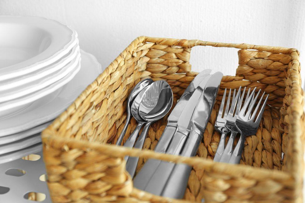 Cutlery in wicker basket on shelf;